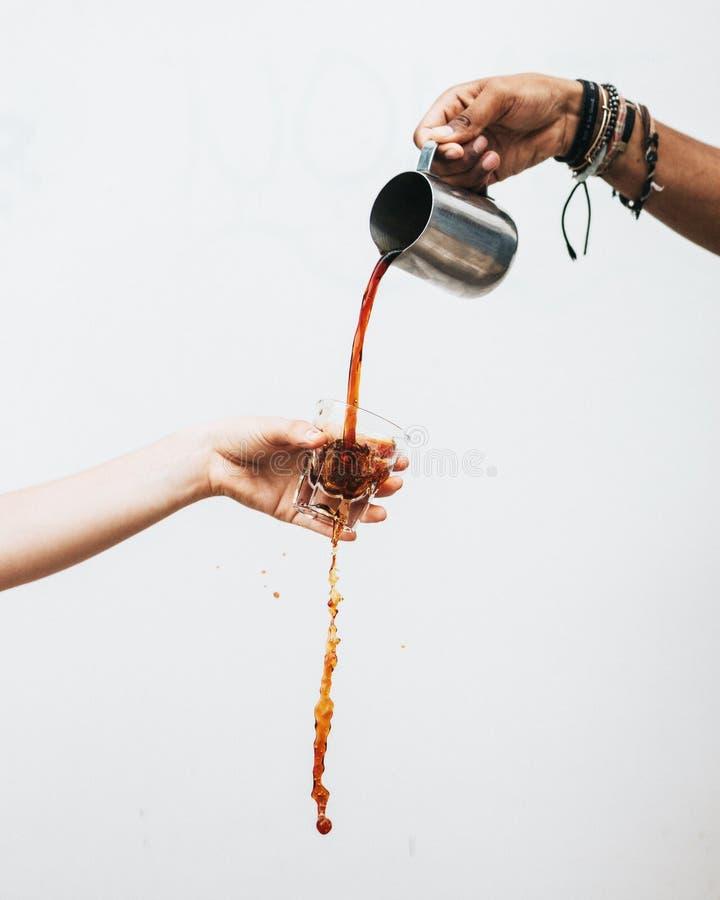 Mans hand som häller en mörk flytande in i ett exponeringsglas som rymms av en kvinnlig med en vit bakgrund fotografering för bildbyråer