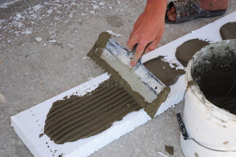 Mans hand som rappar en isolering för väggpolystyren- eller skumbräde med mursleven Polystyrenisolering för källareväggar arkivfoton