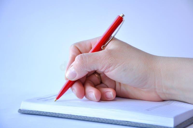 Mans hand som rymmer en penna och skriver i en anteckningsbok arkivbild