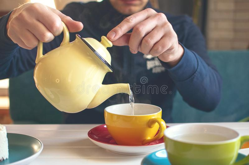 Mans hand with a yellow teapot pours herbal tea into a cup. Tea time in cafe, Tea party. Green honey table detox ginger hot aroma aromatic background beverage stock photo