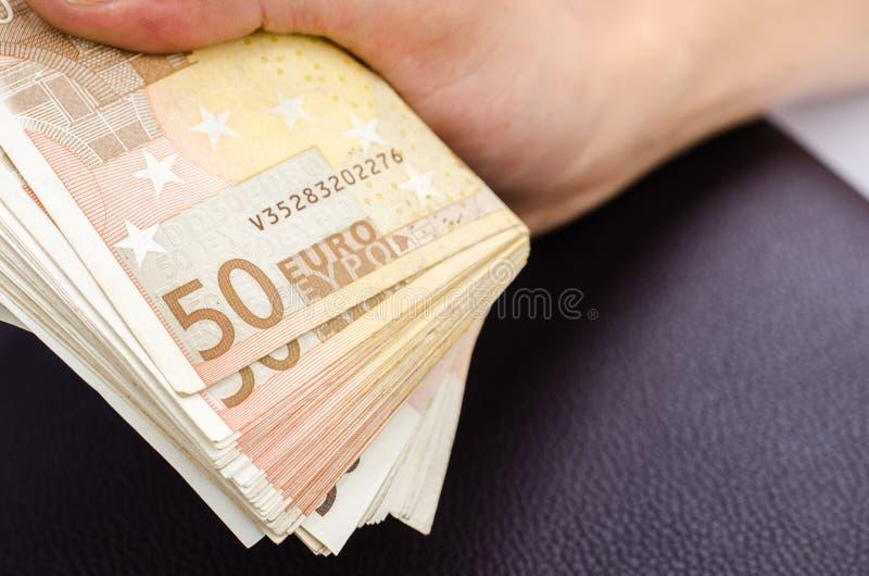 Mans handen som rymmer flera 50 eurosedlar arkivfoto