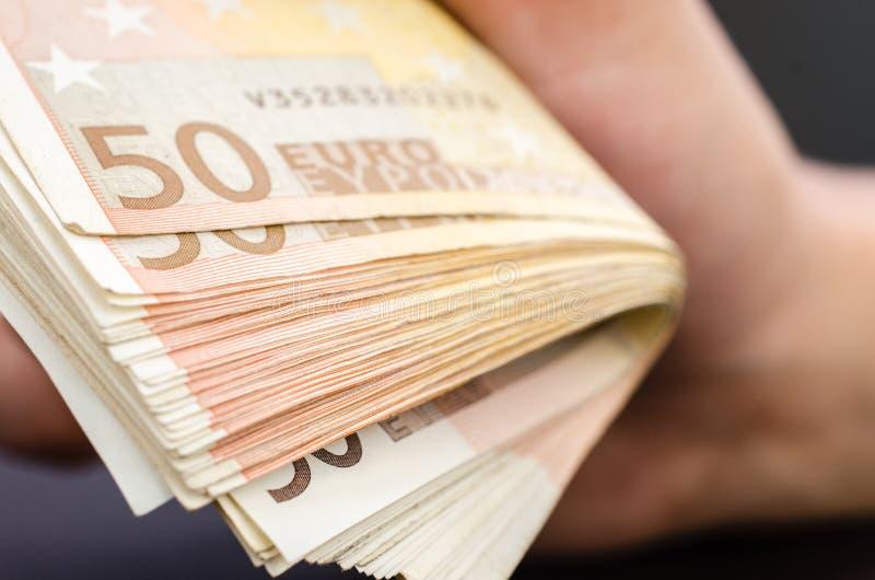 Mans handen som rymmer flera 50 eurosedlar royaltyfria foton