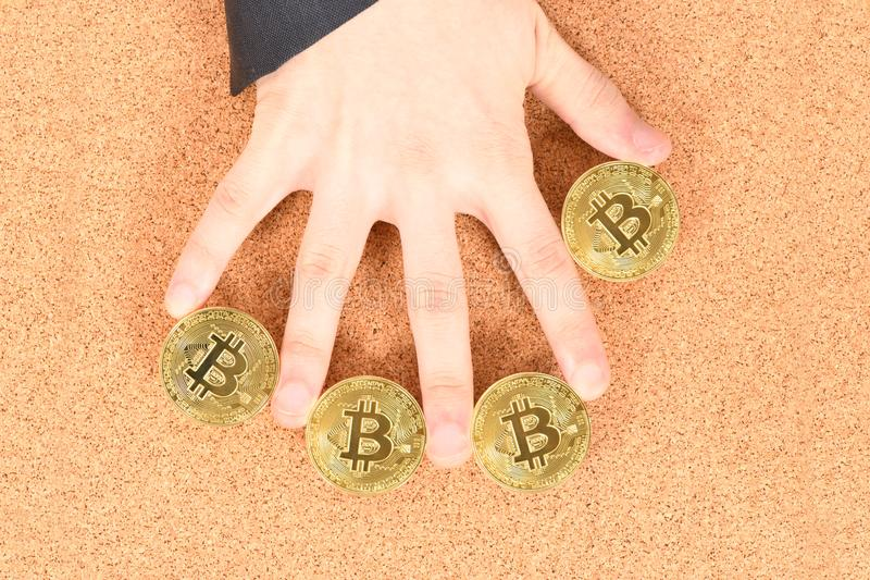 Mans handinnehav guld- Bitcoin p? brun texturerad korkbakgrund royaltyfria foton