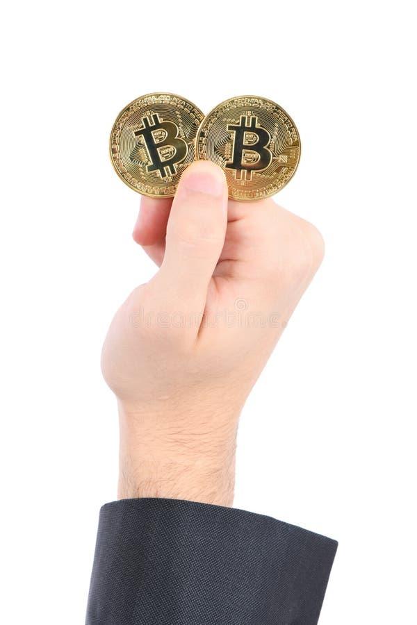 Mans handinnehav guld- Bitcoin p? vit bakgrund royaltyfri fotografi
