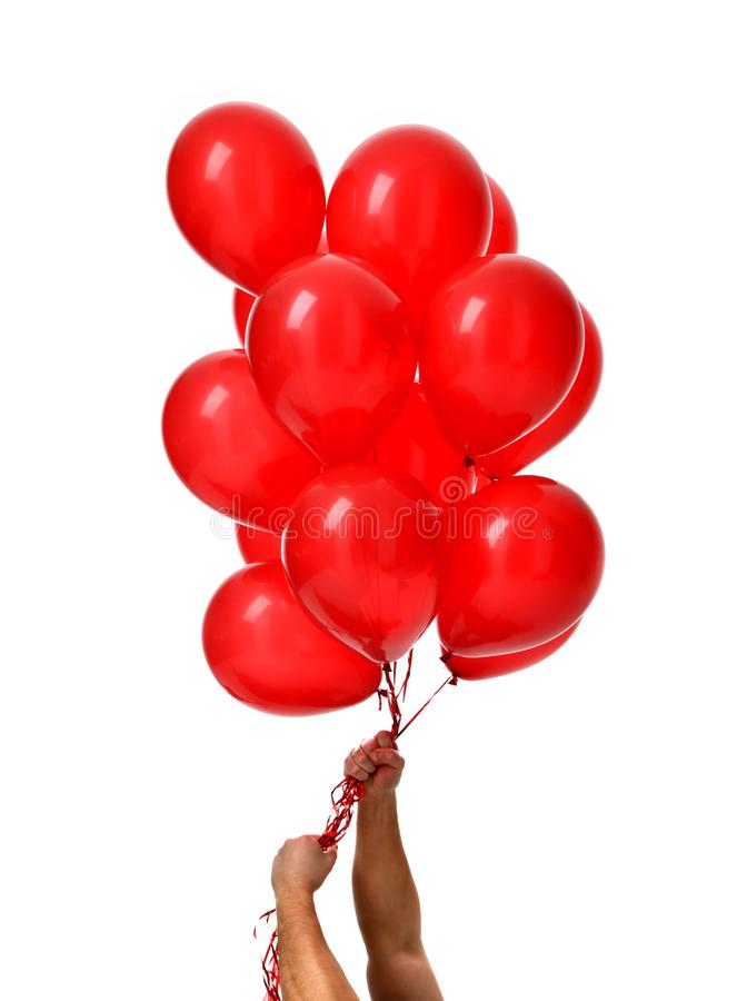 Mans hands hold bunch of big red balloons object for birthday party royalty free stock image