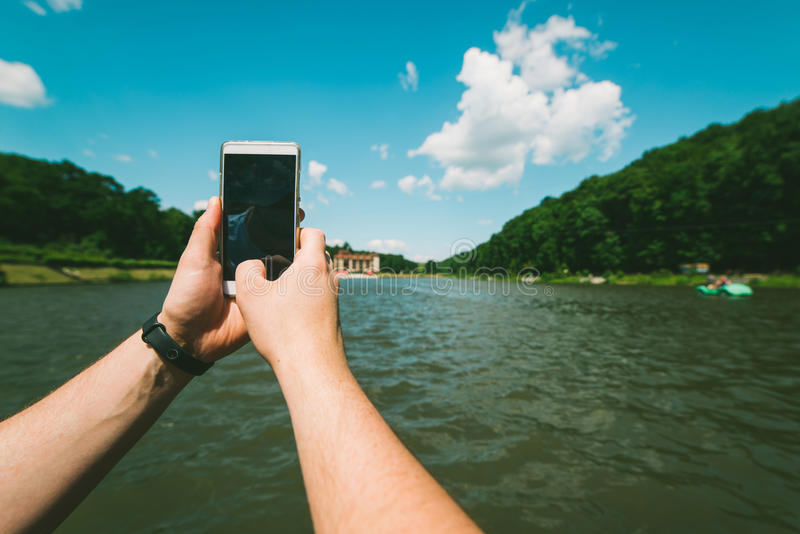 Mans hands hold phone, taking picture of the lake. In sunny day stock image