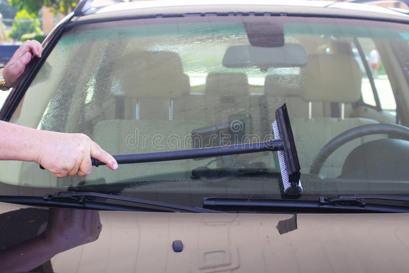 Mans handtvagningvindrutan av bilen på gasstation-GPS sammanträde på streck royaltyfri foto