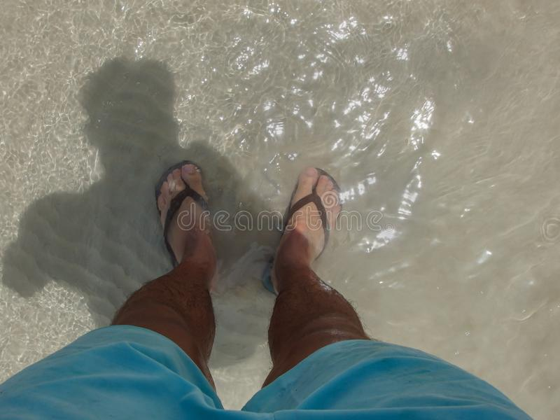 Mans legs wearing flip flops standing in the sea. Mans legs with blue shorts and wearing flip flops, standing in the clear water of the sea in Thailand royalty free stock photography