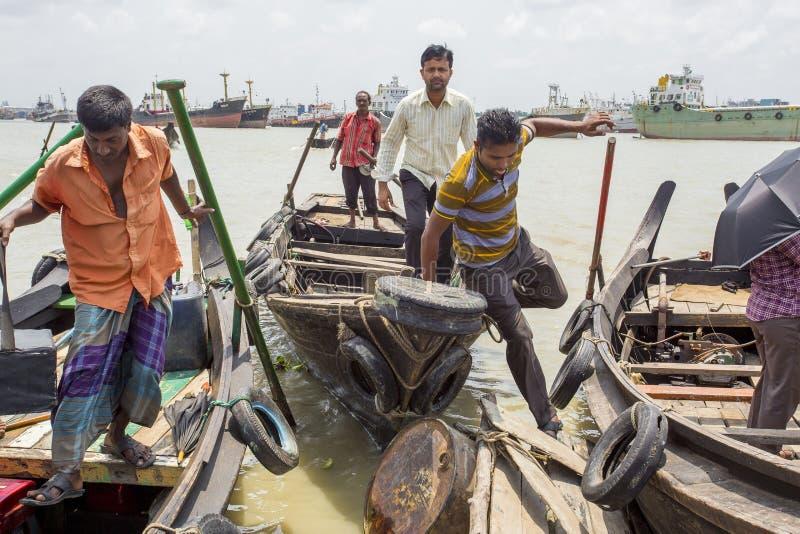 3 mans lyfter på fartyg i Karnafuli flodSadarghat områden, Chittagong, Bangladesh arkivfoton