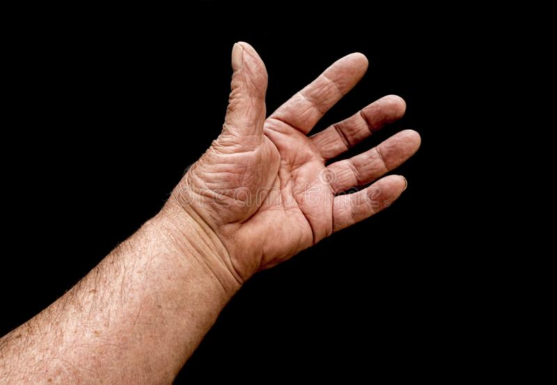 Mans reaching hand. A view of old mans hand reaching out on a black background stock photography