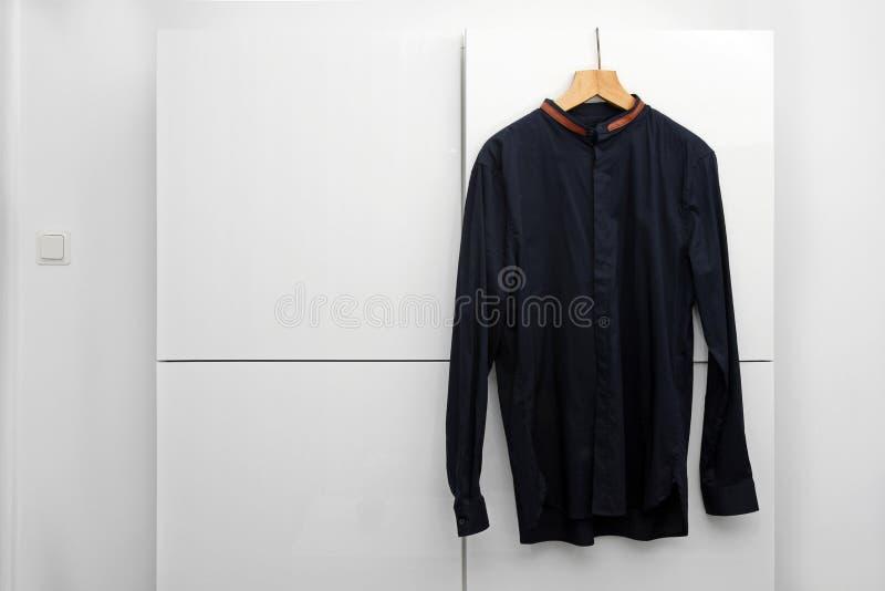 Mans skjorta som hänger på en hängare i garderob arkivfoto