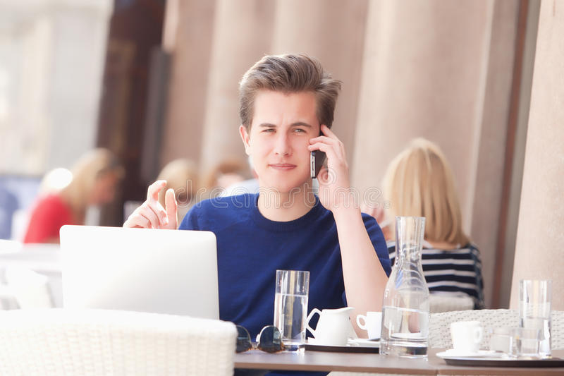 Mansammanträde i det utvändiga kafét som talar på telefonen fotografering för bildbyråer
