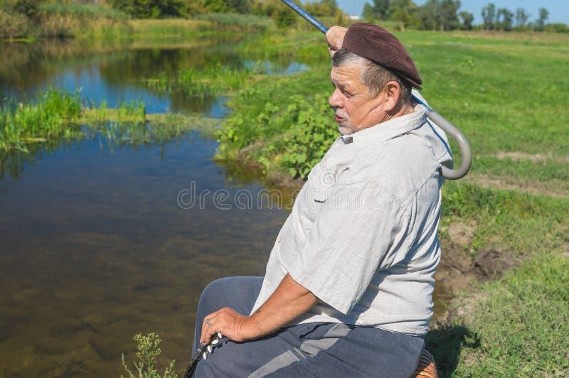 Mansammanträde på en flodstrand på en vide- stol och att skrapa hans baksida med att gå pinnen royaltyfri foto