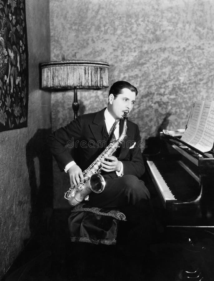 Mansammanträde på pianot som spelar saxofonen (alla visade personer inte är längre uppehälle, och inget gods finns Leverantörgara royaltyfria bilder