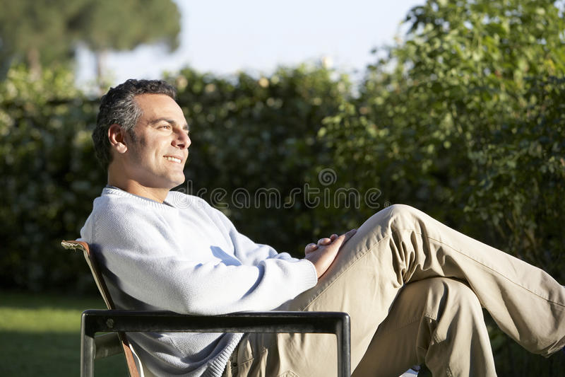 Mansammanträde på stol i trädgård royaltyfria foton