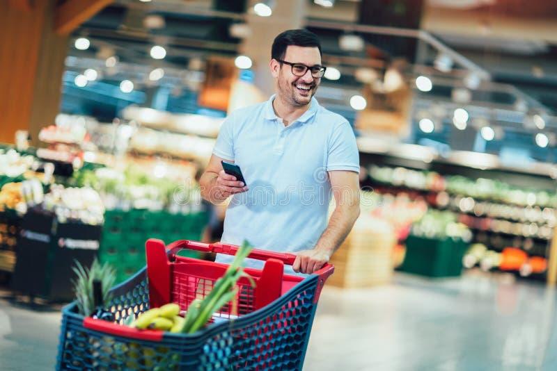 Manshopping i supermarket som skjuter spårvagnen och rymmer telefonen royaltyfri bild