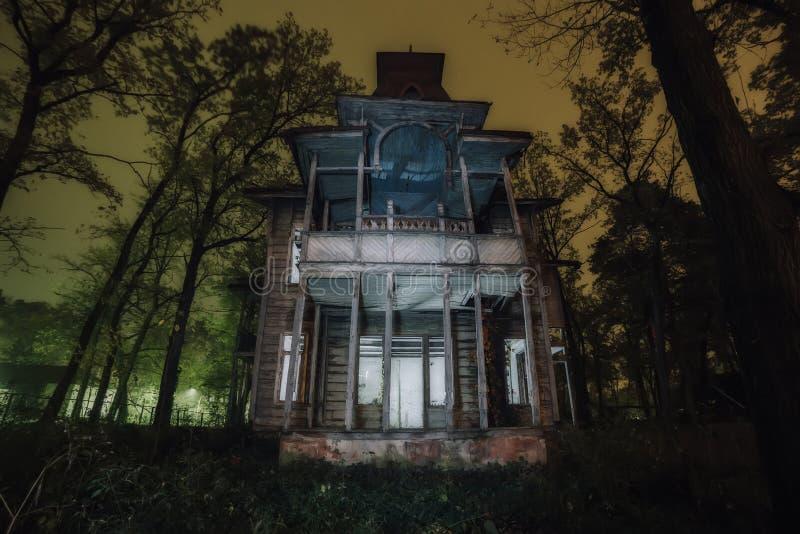 Mansión arruinada frecuentada abandonada de madera espeluznante vieja en la noche imagen de archivo