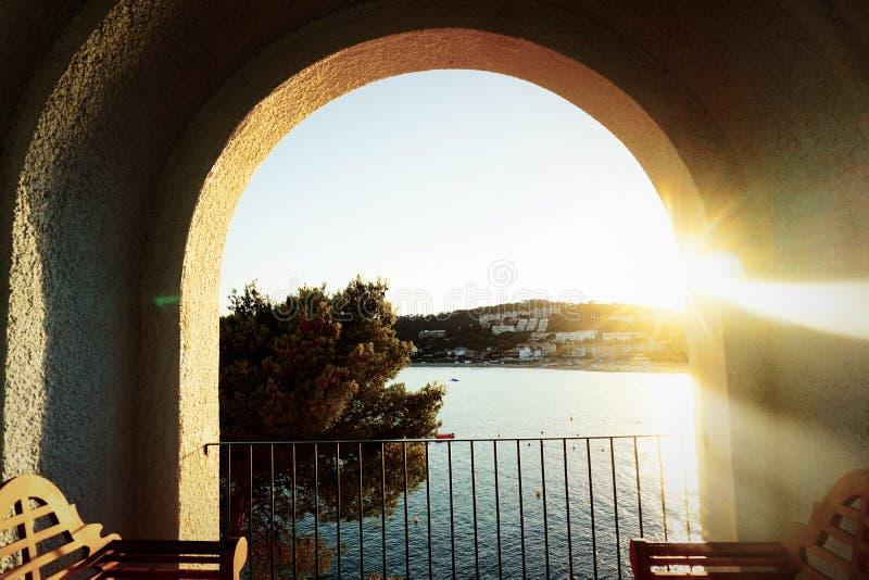 Mansión de Outstaing, con el arco en la orilla de la opinión del mar en la puesta del sol foto de archivo
