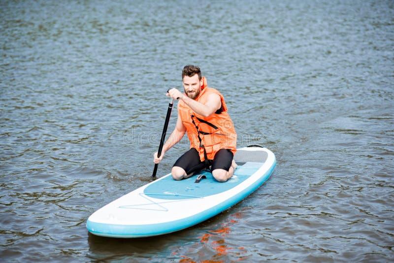 Mansimning på paddleboarden royaltyfri bild