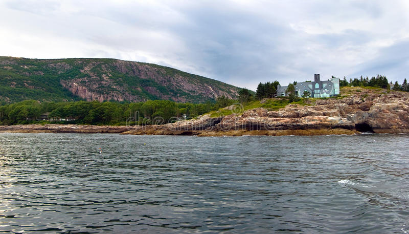 Mansion on the coast Maine. A view from the water of a large, luxurious home on the coast of Maine stock images