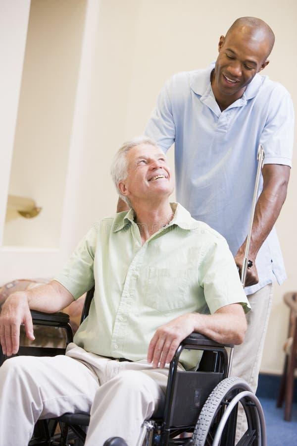 mansjuksköterska som skjuter rullstolen royaltyfria bilder