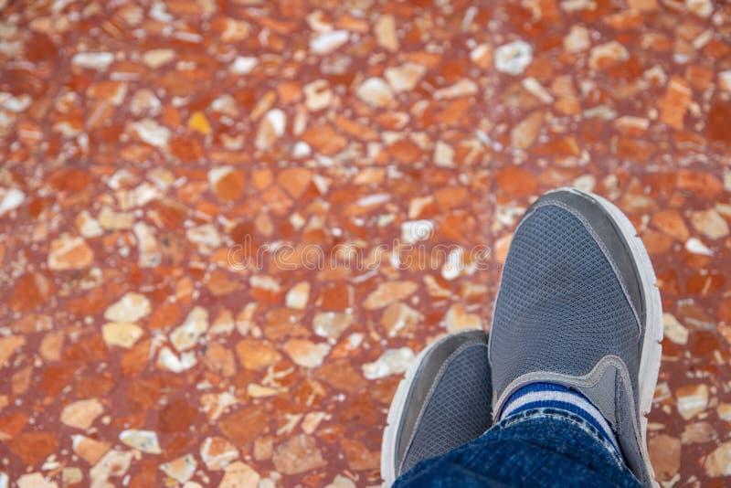 Manskor på golv Selektiv fokus på grå gymnastiksko- eller mäns sommarskor och jeans på suddig färgrik röd brun marmor royaltyfri foto