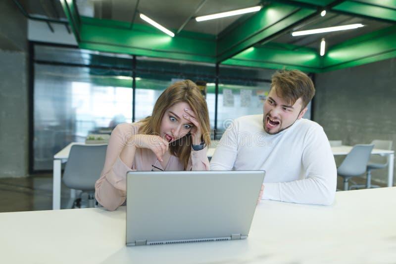 manskrin för en flicka, som sitter på en dator, ett fel på arbete Framstickandesvetsningsarbetare Agression i kontoret arkivbilder