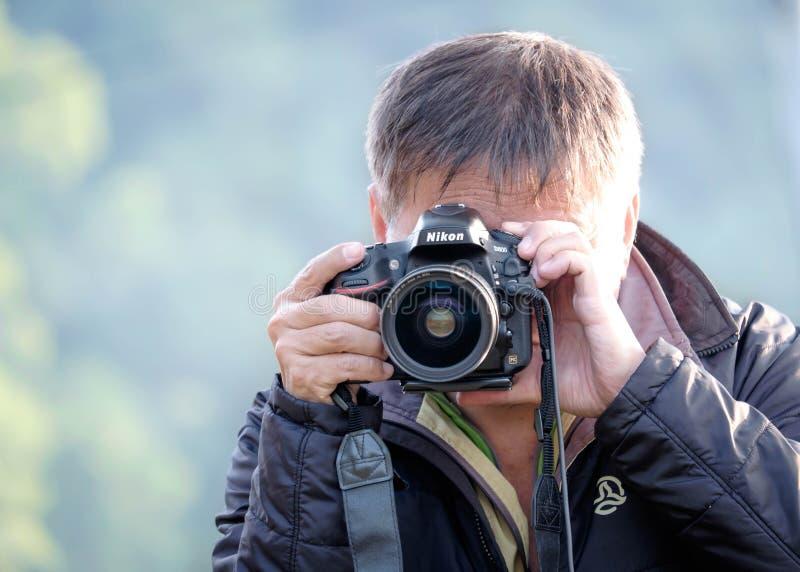 Manskytte med en Nikon DSLR kamera royaltyfri foto