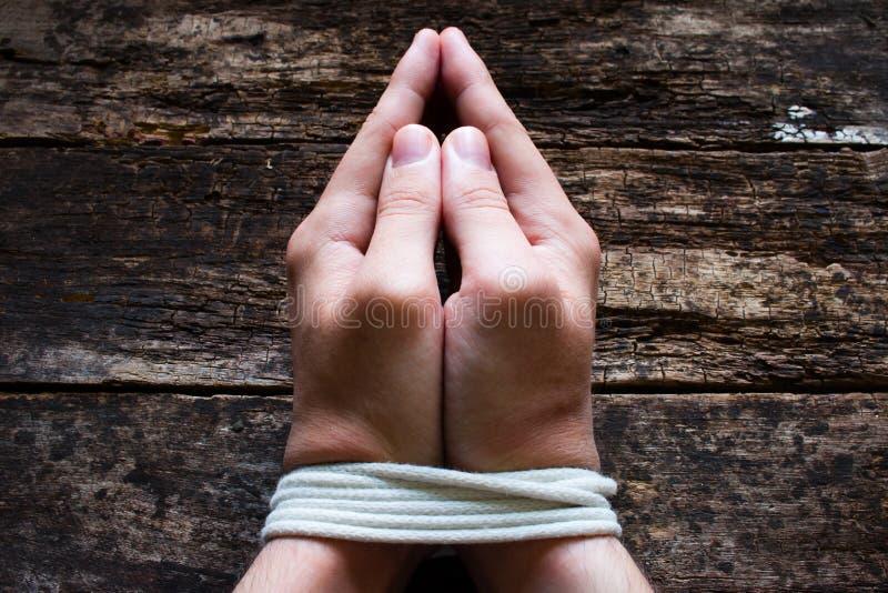 Manslaven ber med hans bundna händer arkivbild