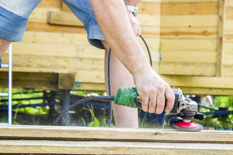 Mansnickarebyggmästaren polerar brädena med en elektrisk maskin för malande diskett Sommar i bakgrunden är a arkivfoto