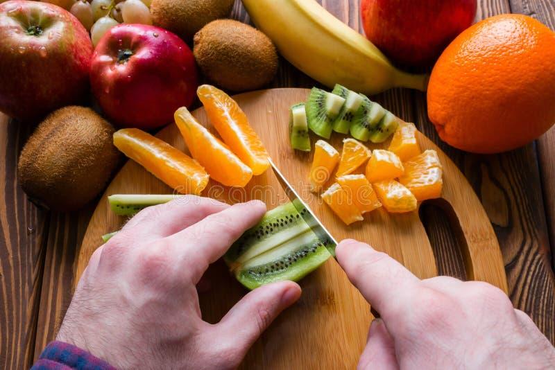 Mansnittfrukt på en skärbräda arkivfoton