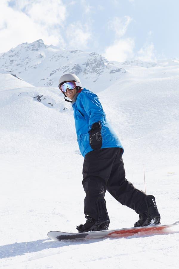 ManSnowboarding på Ski Holiday In Mountains royaltyfri fotografi