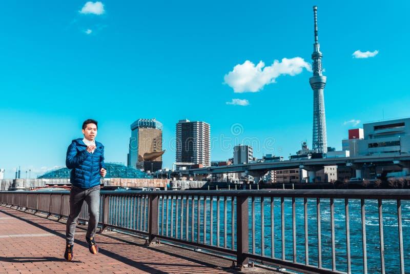 Manspring förbi den Sumida floden, Tokyo Skytree i bakgrund Sportutbildning, sund livsstil eller Tokyo 2020 sommar olympiskt begr arkivbild