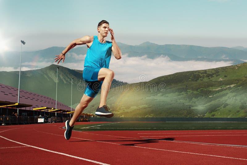 Manspring i spåret Färdig manlig konditionlöpare som joggar i stadion royaltyfri fotografi