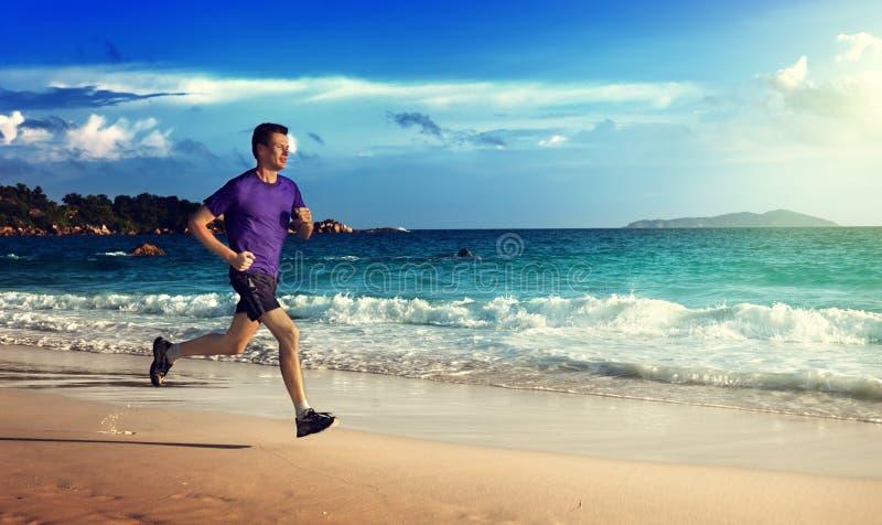 Manspring på den tropiska stranden royaltyfri fotografi