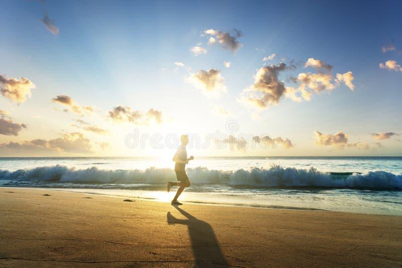 Manspring på den tropiska stranden på solnedgången arkivbilder