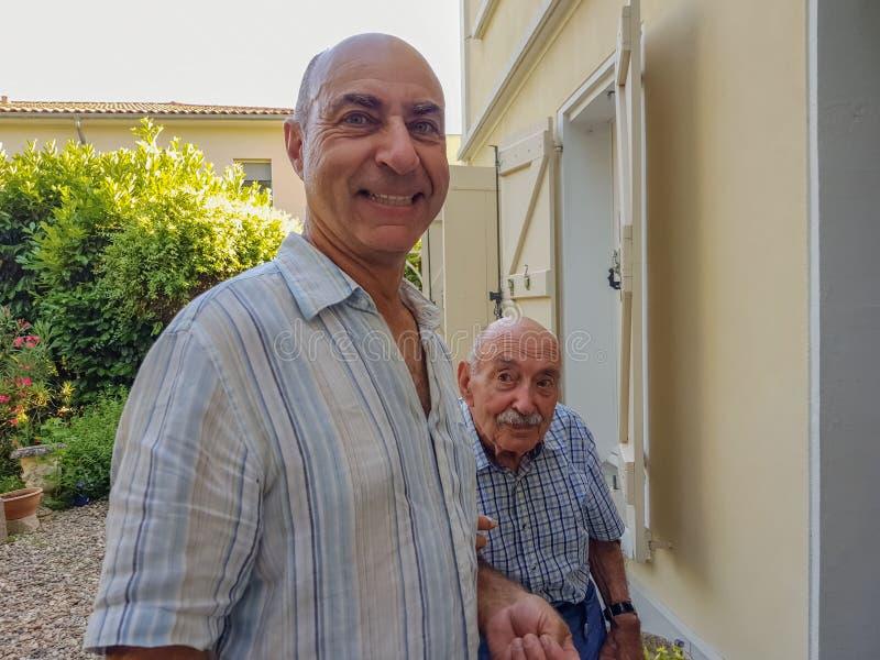 manstående två Den äldre sonen stöttar hans gamla fader och hjälper hans royaltyfria bilder