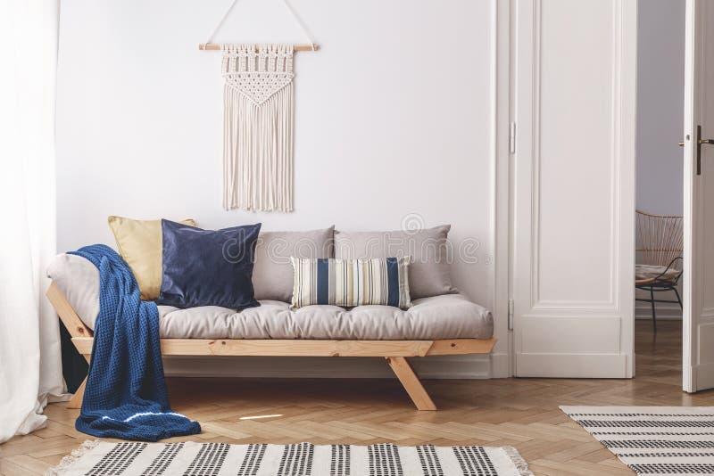 Manta azul y almohadas en el sofá de madera gris en el interior blanco de la sala de estar con la puerta Foto verdadera fotos de archivo