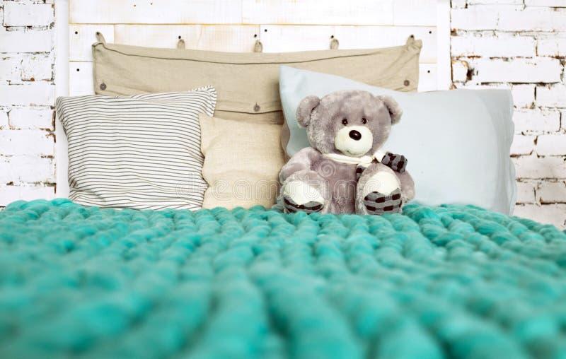 Manta de la lana merina en cama con las almohadas en colores en colores pastel y Ted fotografía de archivo