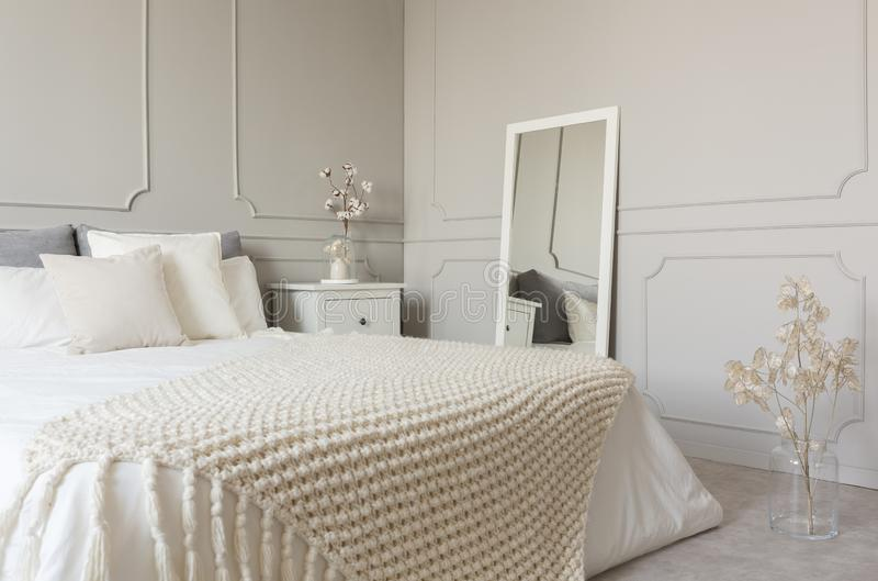 Manta de lana beige en el lecho blanco de la cama gigante en el dormitorio de moda interior con la pared gris imagen de archivo libre de regalías