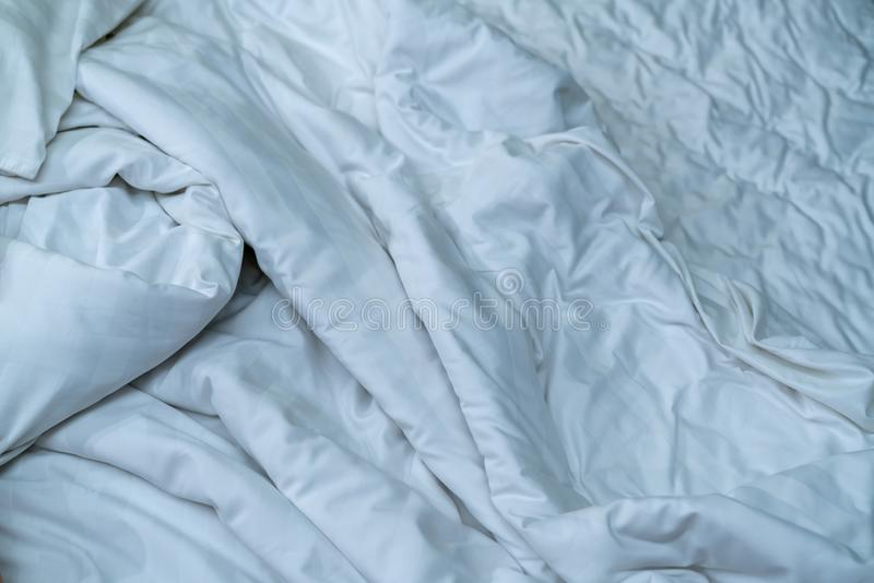 Manta de lino blanca en dormitorio del hotel Detalle ascendente cercano de la manta blanca sucia después de despertar por mañana  fotos de archivo