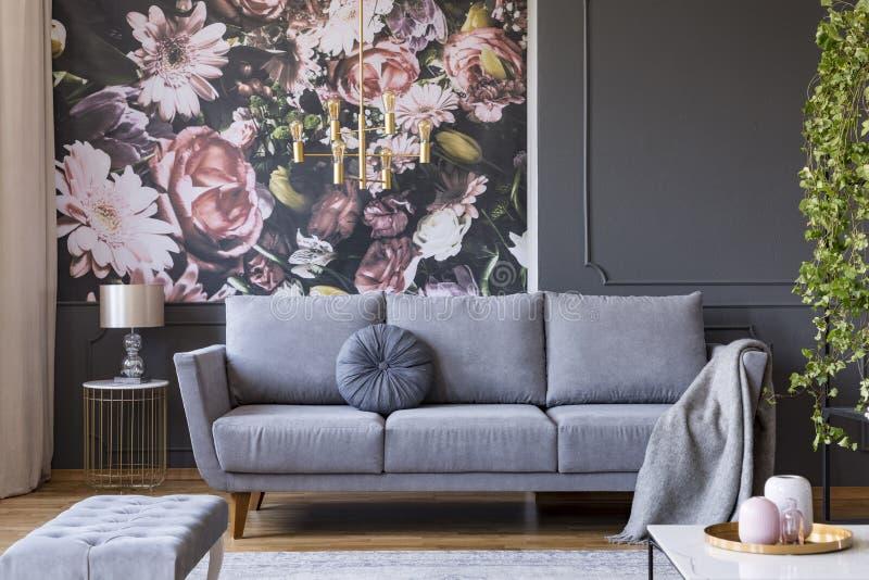 Manta en el sofá gris en interior de la sala de estar con el wallp de las flores fotos de archivo
