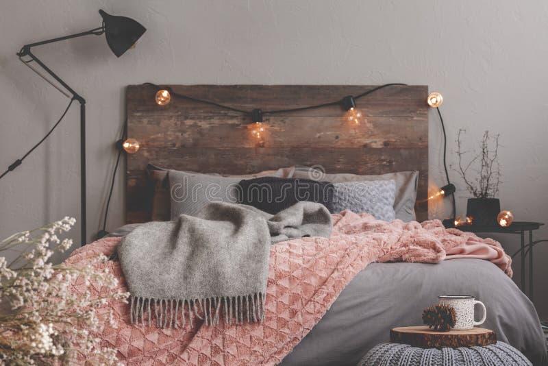 Manta gris y rosa pastel sobre cama gris de una habitación de diseño rústico foto de archivo