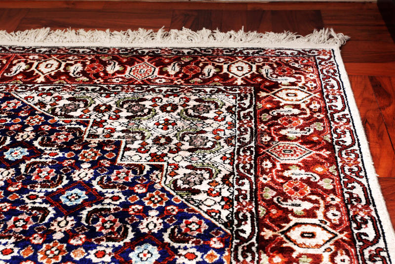 Manta oriental persa en piso de madera imagen de archivo
