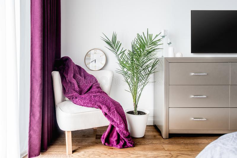 Manta púrpura y un reloj de pared como decoración en dormitorio moderno, elegante fotografía de archivo