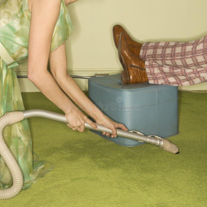 Manta que limpia con la aspiradora de la mujer. imagen de archivo libre de regalías