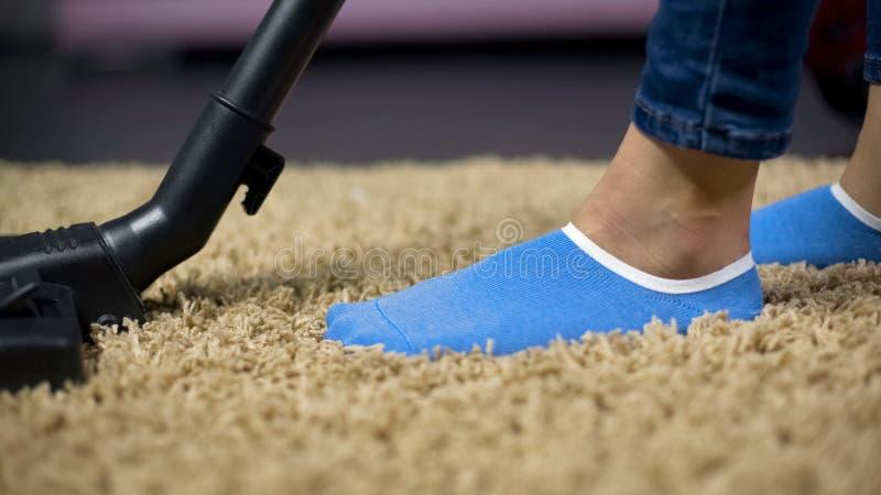 Manta que limpia con la aspiradora femenina para prevenir la reacción de la alergia, quitando la suciedad de la alfombra fotos de archivo libres de regalías