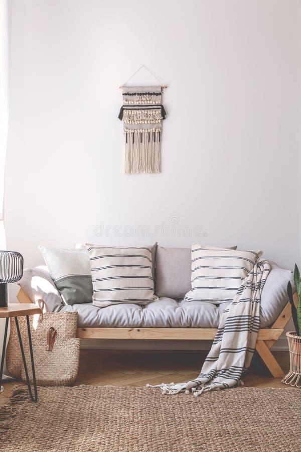 Manta y amortiguadores en el sofá de madera en interior beige de la sala de estar con la alfombra marrón Foto verdadera foto de archivo libre de regalías