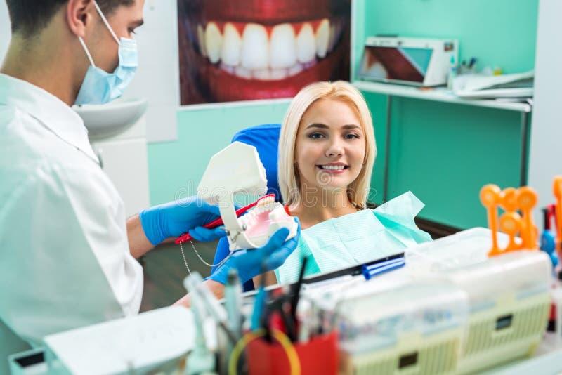 Mantandläkare med handskar som visar på en käkemodell hur man gör ren tänderna med tandborsten riktigt och rätt arkivfoton