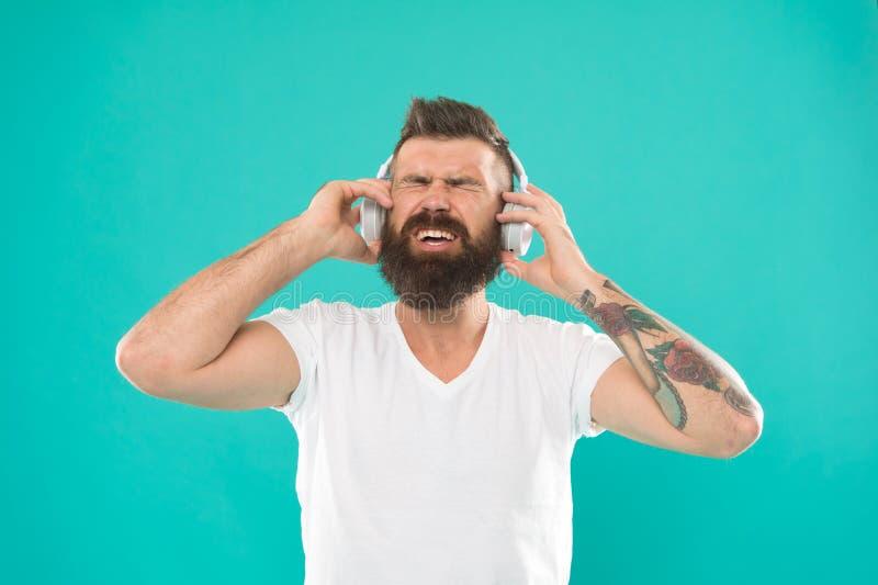 Mante della musica alla moda e bello Uomo in cuffie Le fonti online libere tutte di musica funzionano diversamente poco pezzo ed  immagine stock libera da diritti